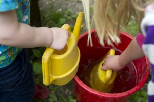 Barnen tar gemensamt ansvar för att vattna blommor och växter i landet.